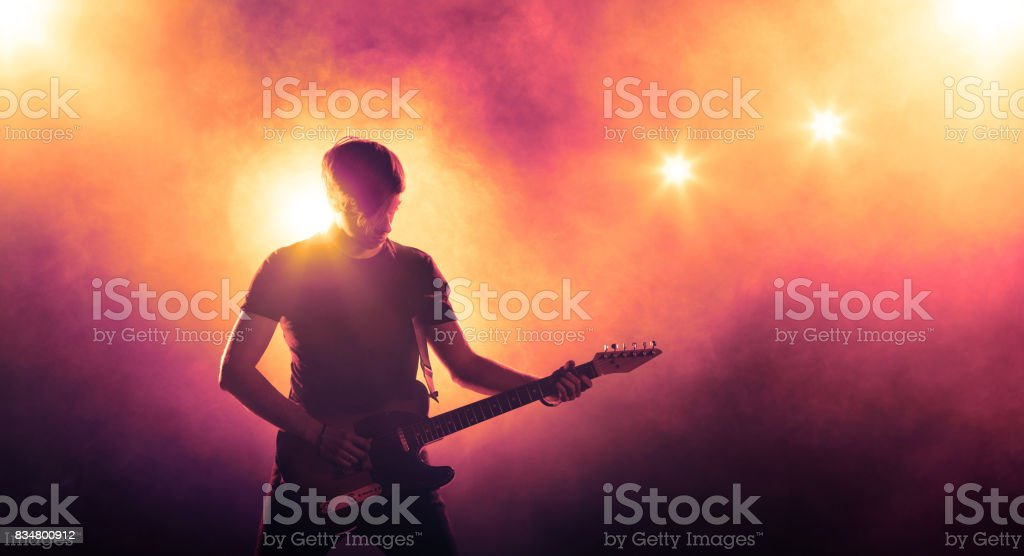 Musician playing the guitar on stage stock photo