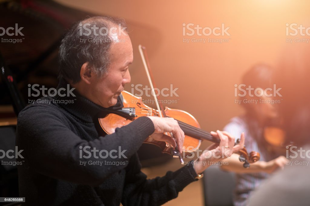 Musician playing violin on concert stage stock photo