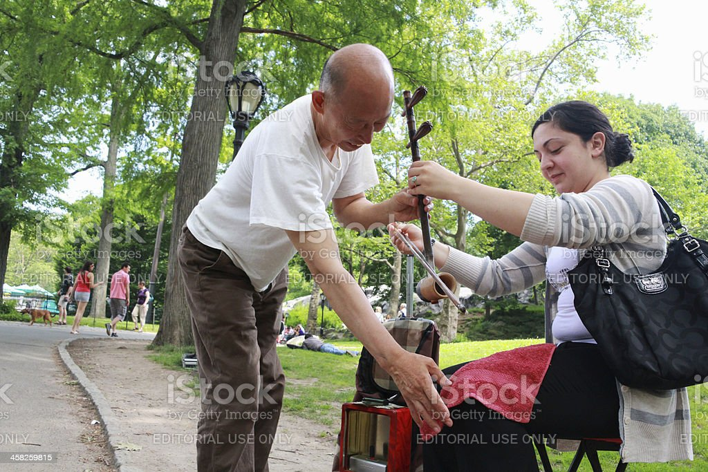 Musician teaching a female how to setup and play Erhu royalty-free stock photo