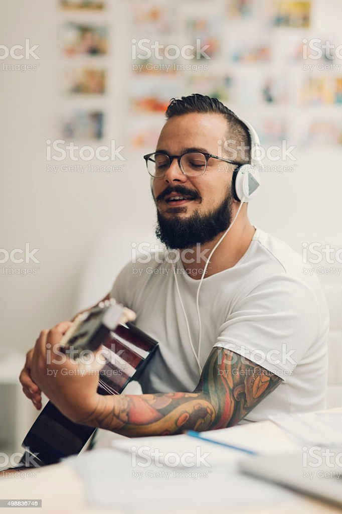 Musician Writing Song In His Recording Studio. stock photo