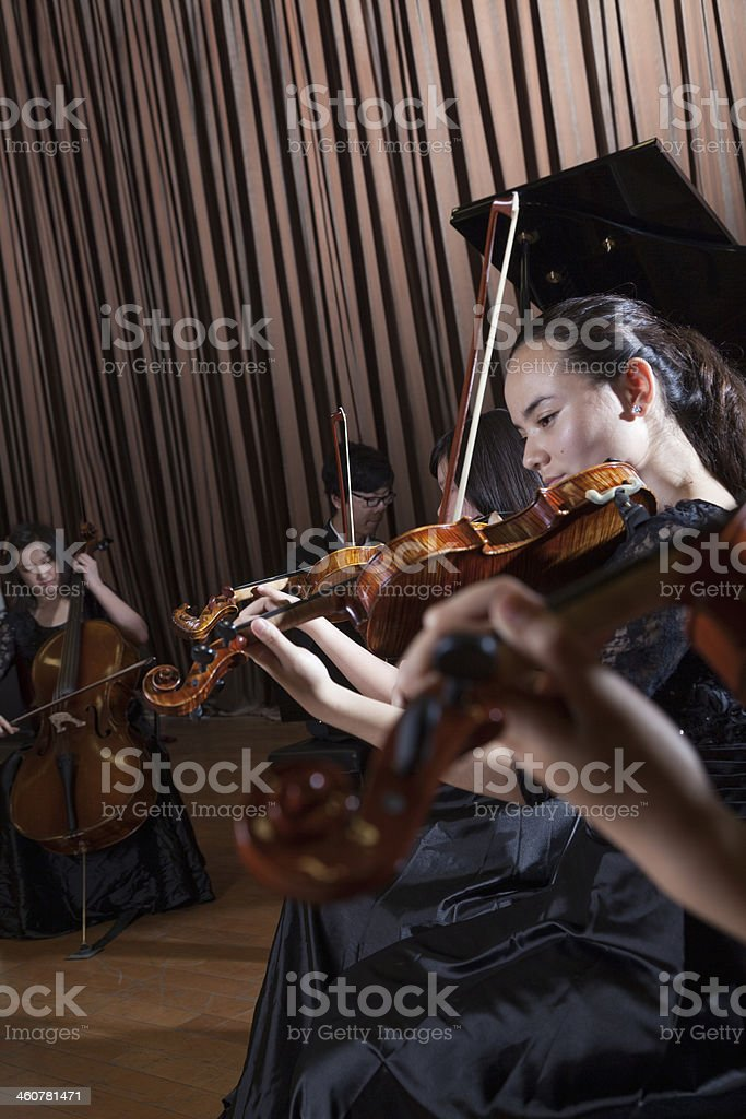 Musicians playing during a performance, violinists at the front stock photo