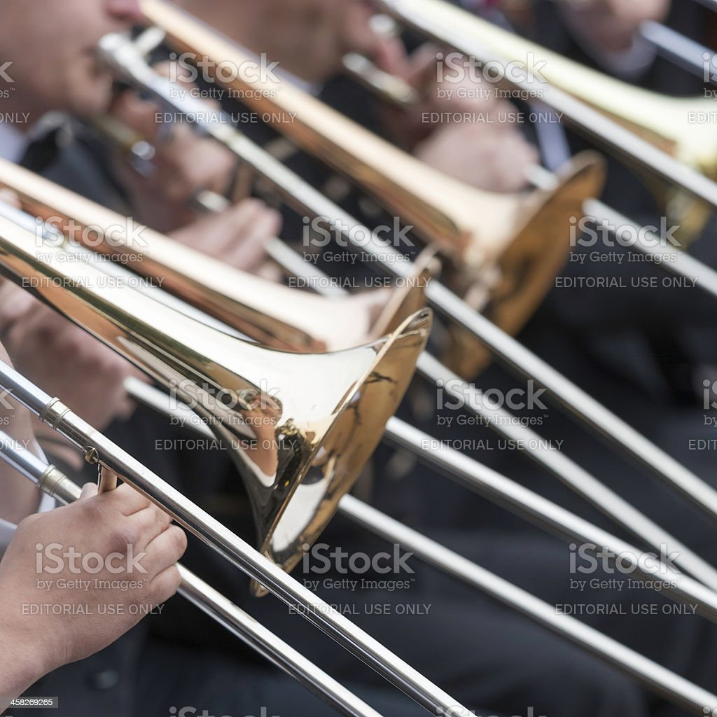 Musicians playing trombones in orchestra at outdoor concert, square close-up stock photo