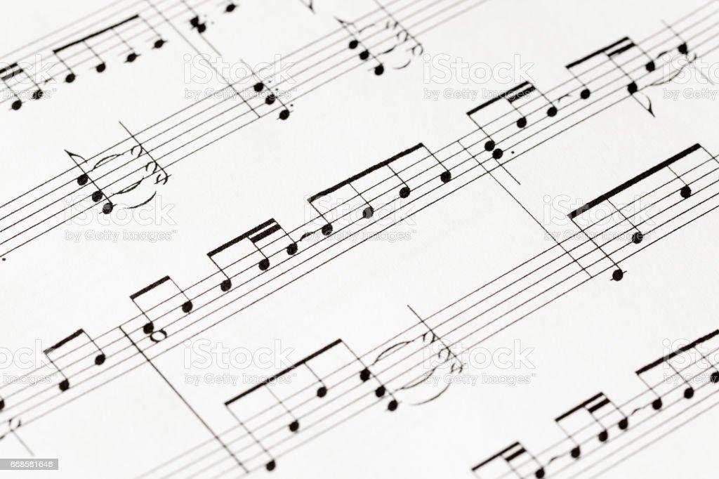 music-notes on white paper macro stock photo