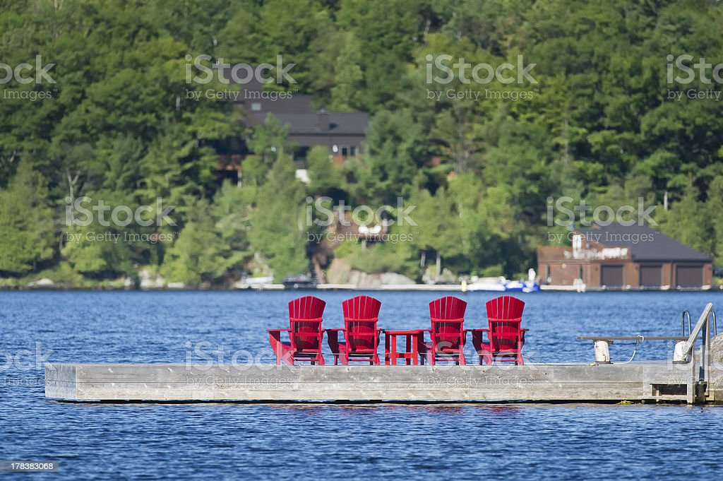 Muskoka chairs on a dock stock photo