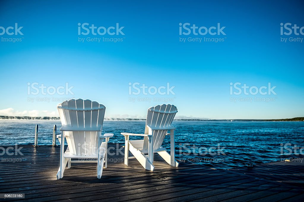 Muskoka chairs on dock on lake in morning stock photo