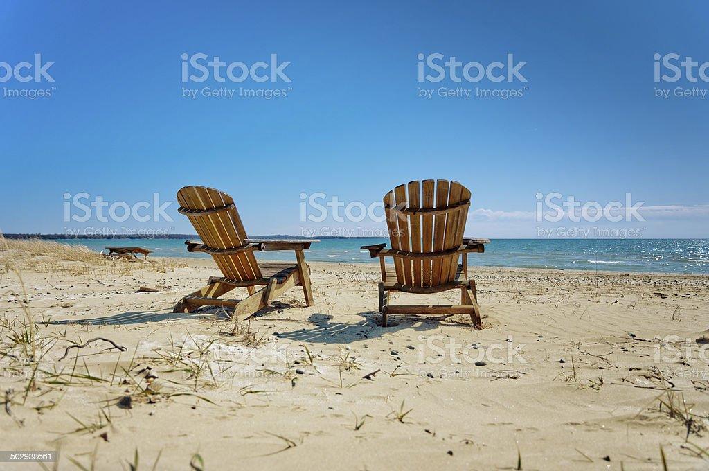 Muskoka chairs on sandy beach stock photo
