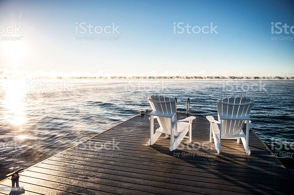 Muskoka chairs on the dock on georgian bay stock photo