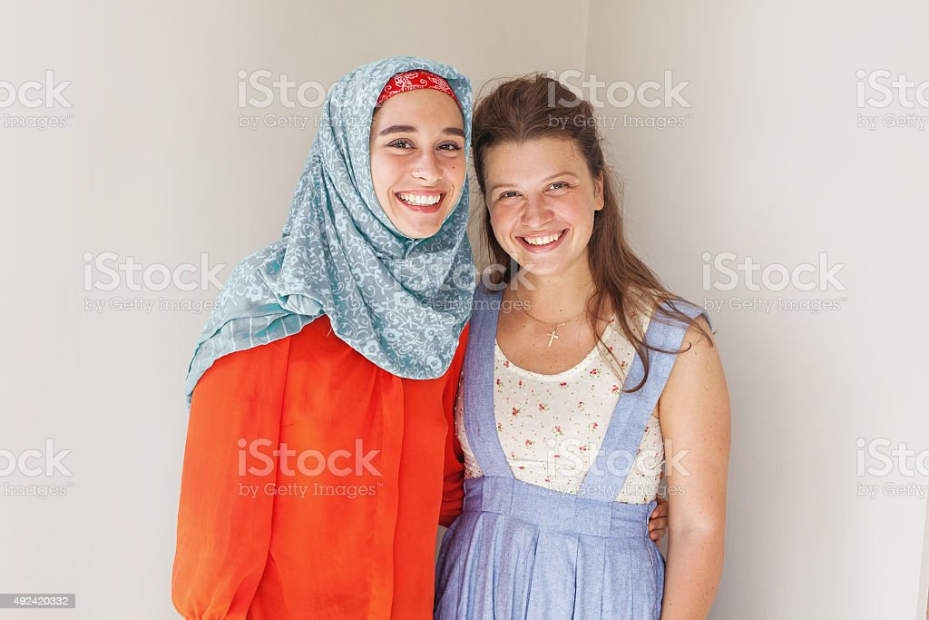muslim and christian girl together stock photo