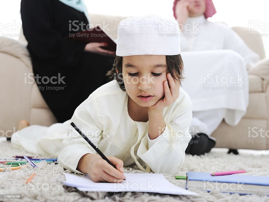 Muslim boy doing homework in front of parents stock photo
