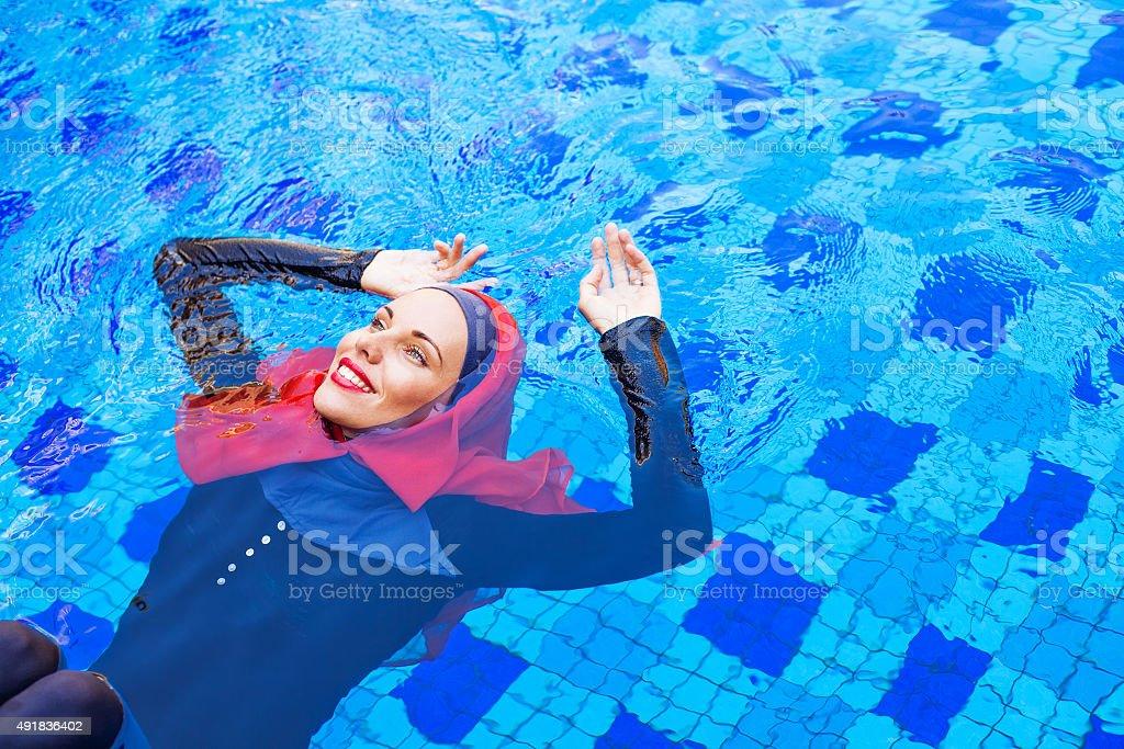 muslim caucasian woman swimming in a swimming pool stock photo