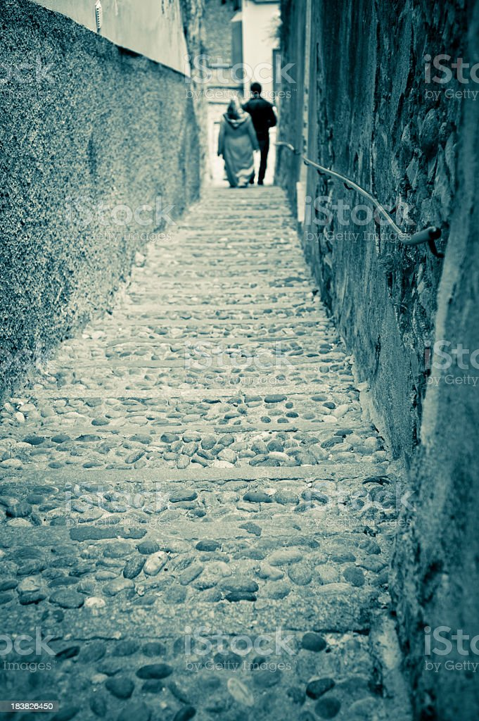 Muslim Couple Walking In A Narrow Italian Rustic Alley stock photo
