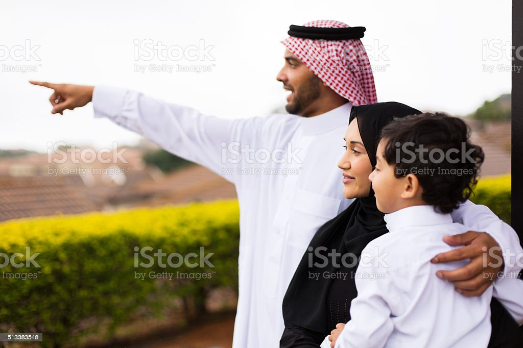 muslim family outside their home pointing stock photo