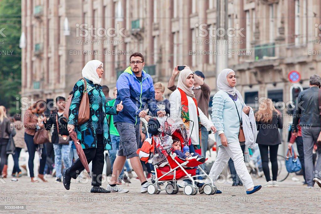 Muslim family walk on the Amsterdam Dam Square stock photo