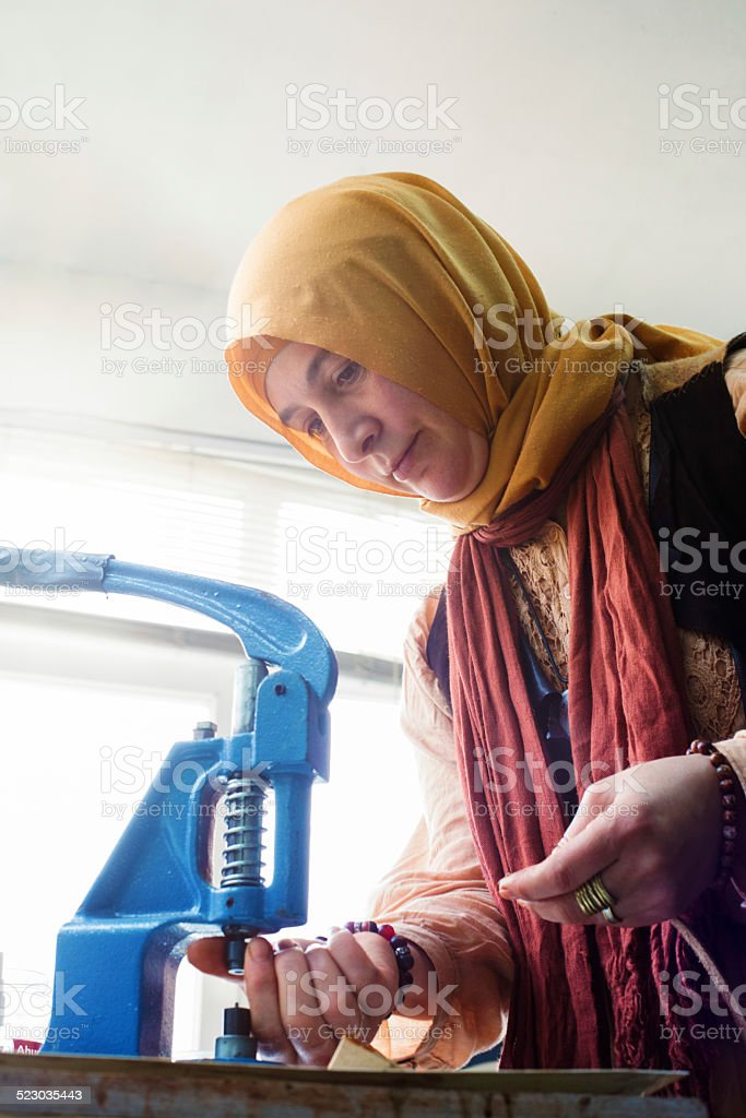 Muslim female leather worker adjusting buttons on her press stock photo