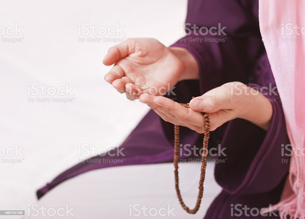 Muslim girl in purple robe praying on white stock photo