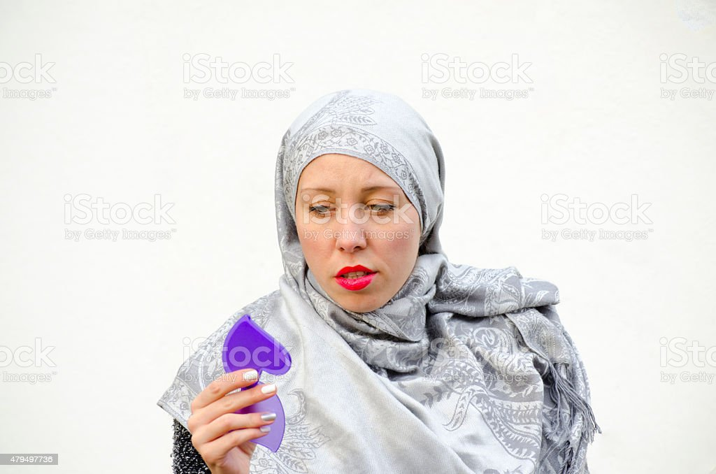 Muslim girl looking at herself in the mirror royalty-free stock photo