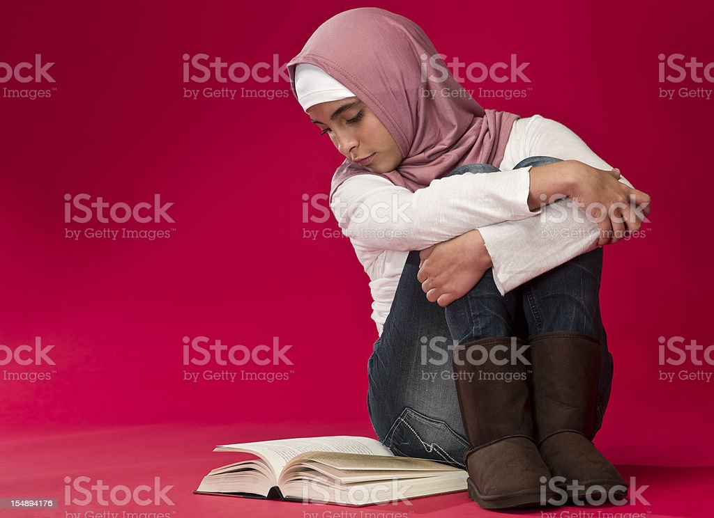 Muslim girl reading a book stock photo