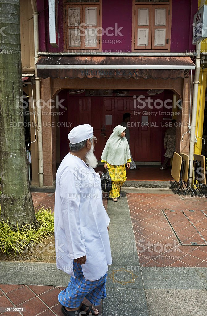 Muslim man and woman walking Singapore stock photo