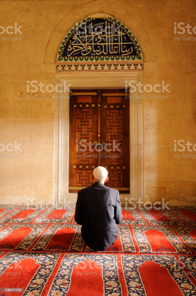 A Muslim man praying in a mosque stock photo