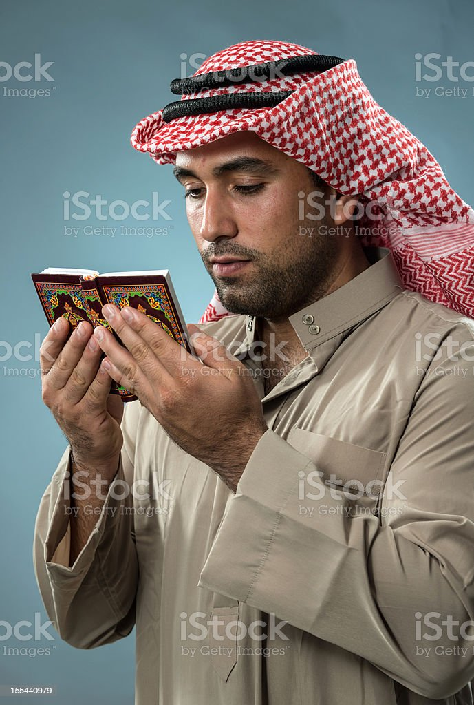 Muslim man reading the Koran stock photo