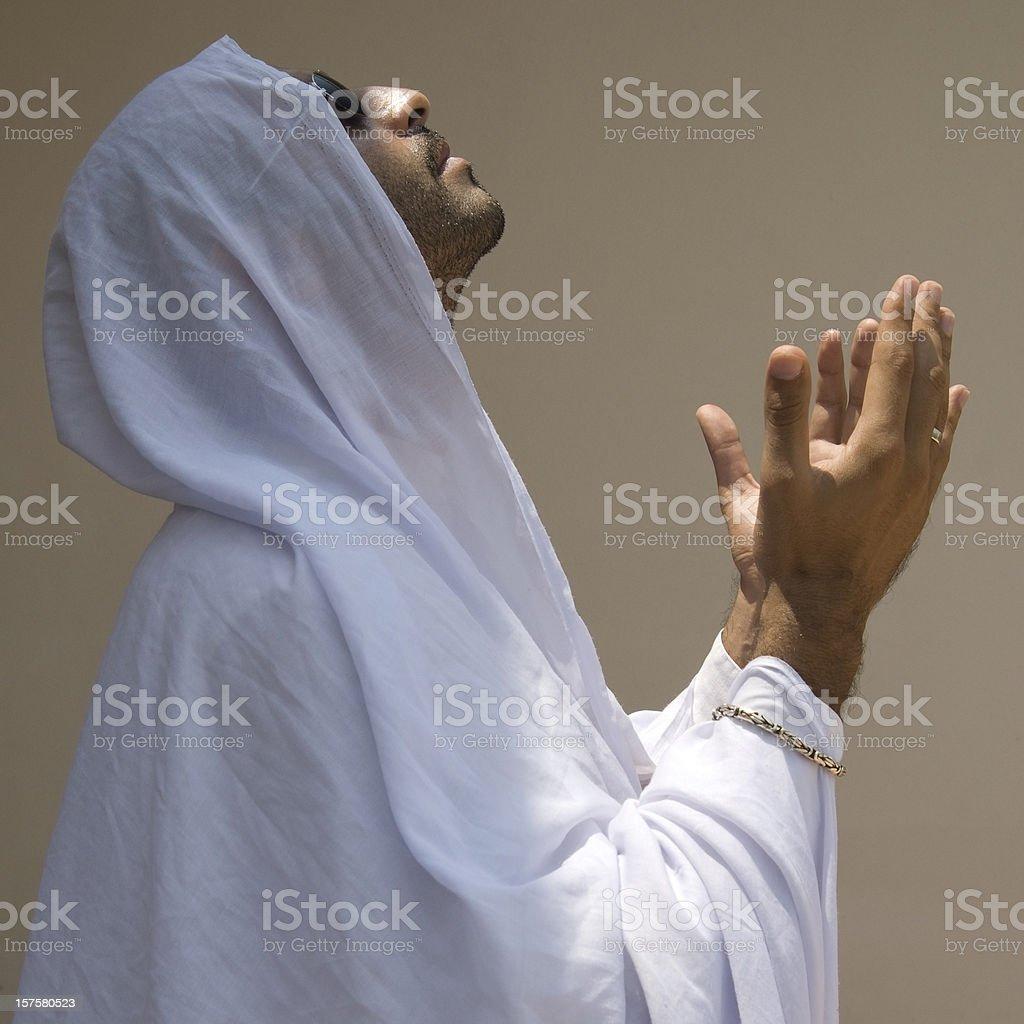Muslim man wearing a white dress praying for God stock photo