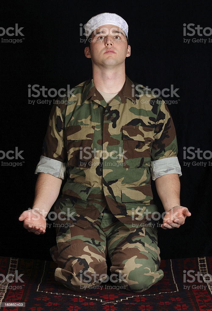 Muslim Military Man Faces Mecca to Pray stock photo