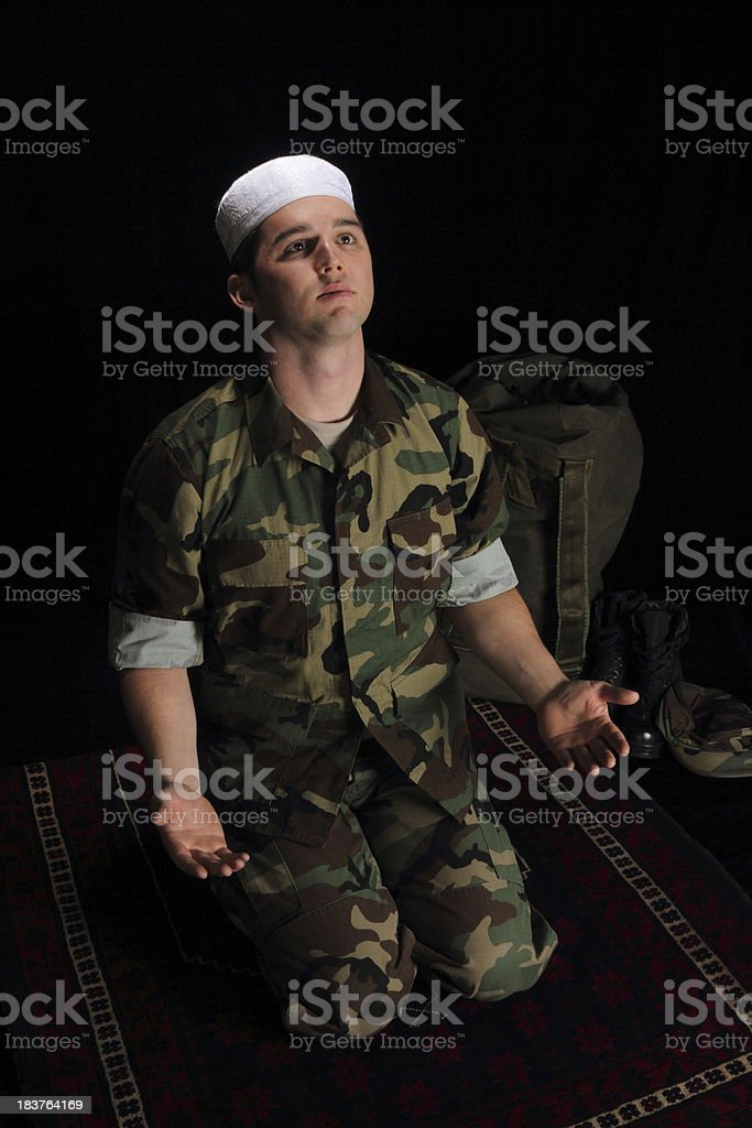 Muslim Military Man Prays on Carpet Vertical stock photo