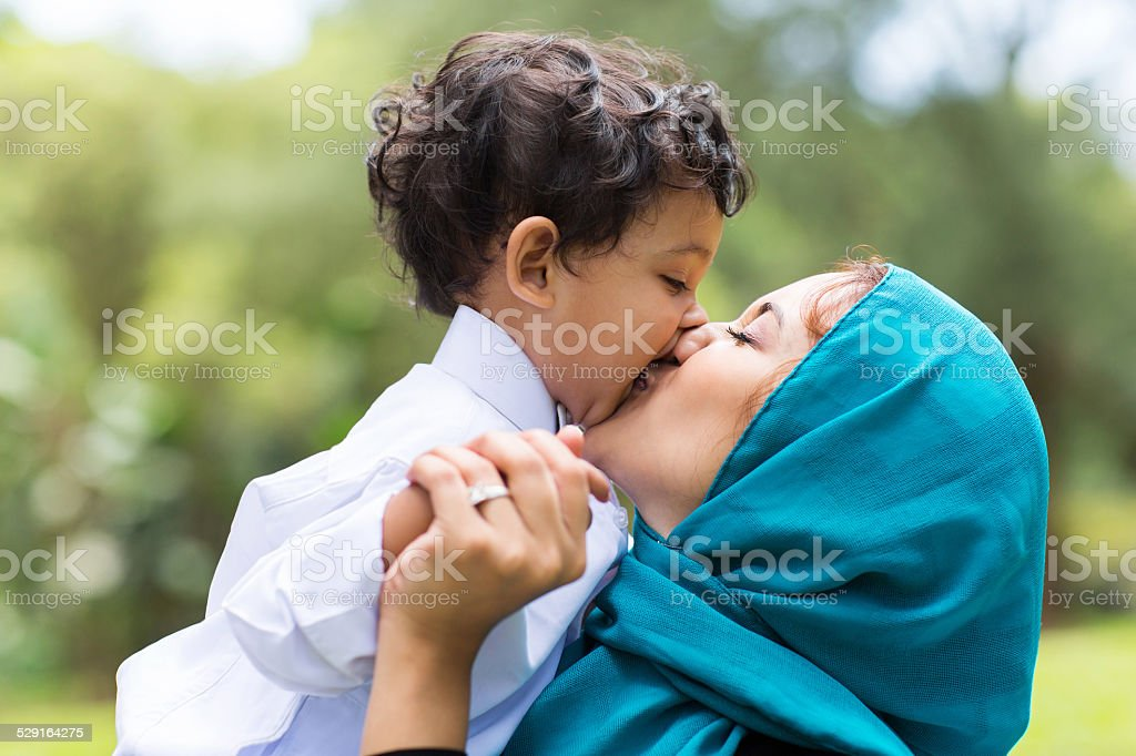 muslim mother kissing her baby boy stock photo