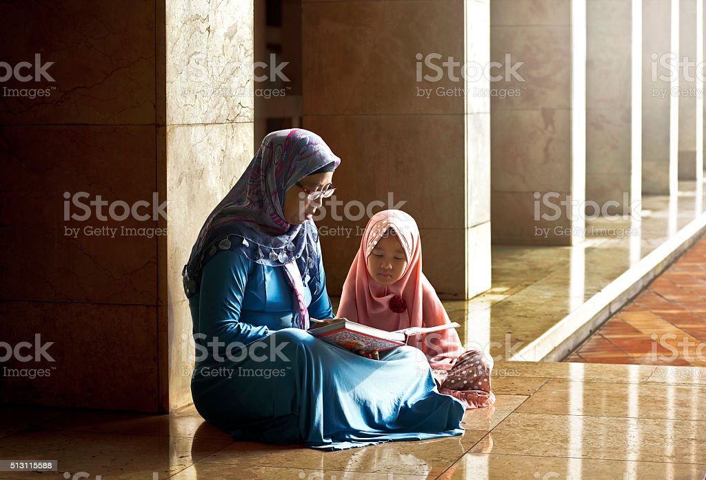 Muslim mother teach her daughter reading koran stock photo