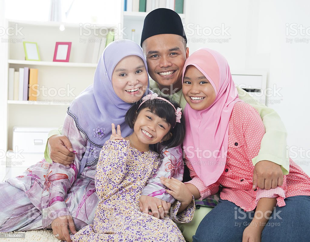 Muslim parents embracing their two daughters stock photo