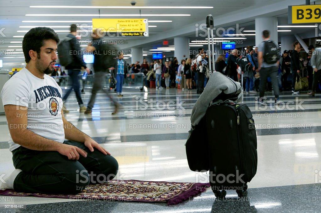 Muslim Praying in Airport stock photo