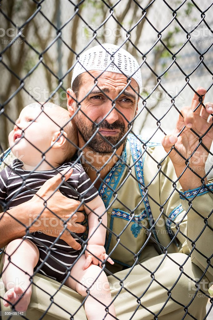 Muslim refugee holding his baby stock photo