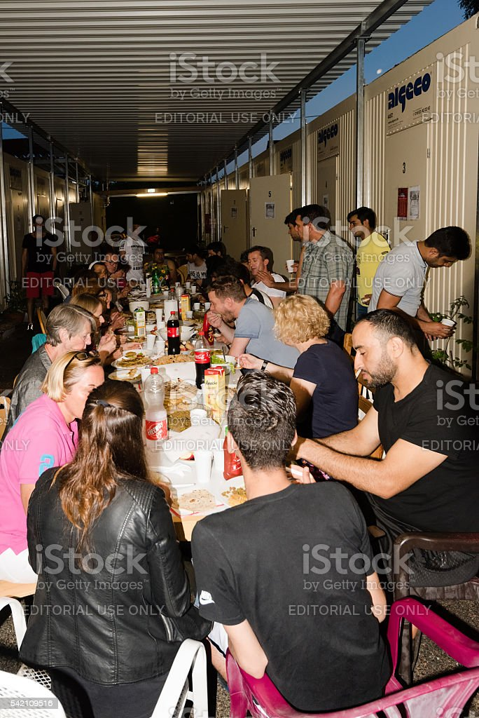 Muslim refugees and German volunteers sit together eating dinner during stock photo
