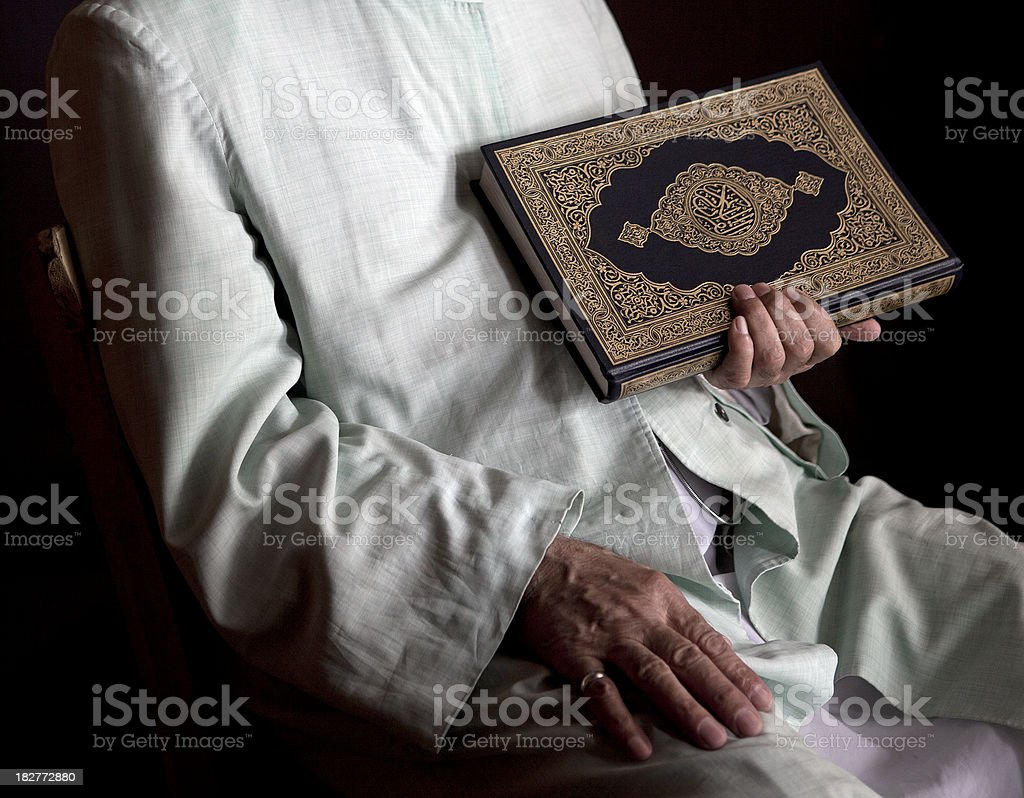 Muslim senior adult holding koran stock photo