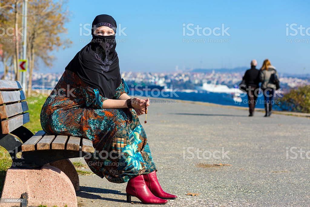 Muslim Style dressed Lady sitting on wooden Bench stock photo