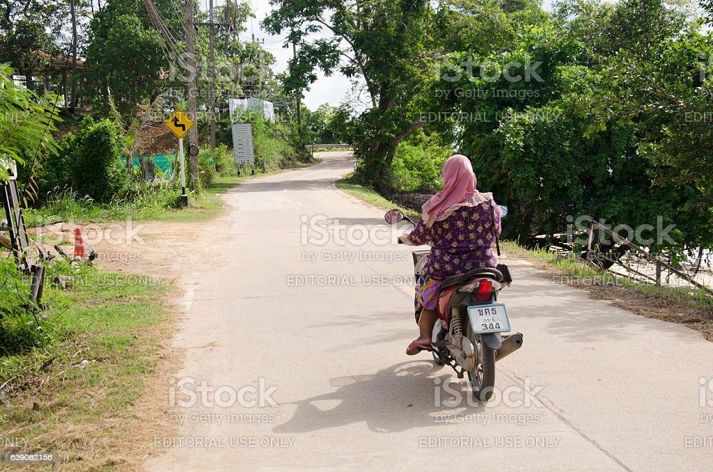 Muslim Thai woman people riding motorcycle on street stock photo
