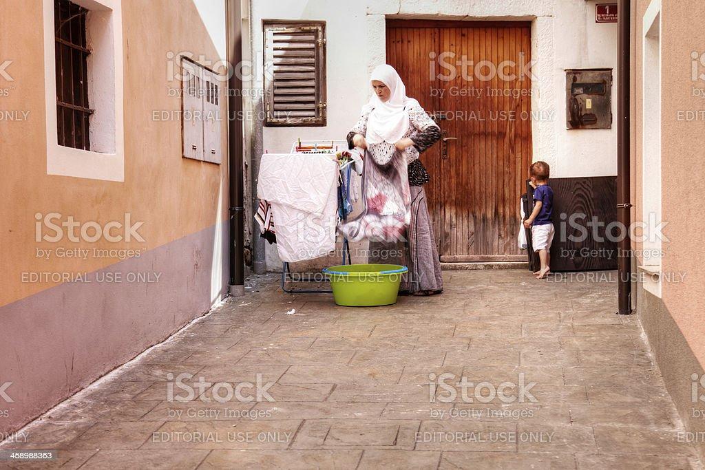 Muslim woman doing laundry chores on Slovenian street royalty-free stock photo