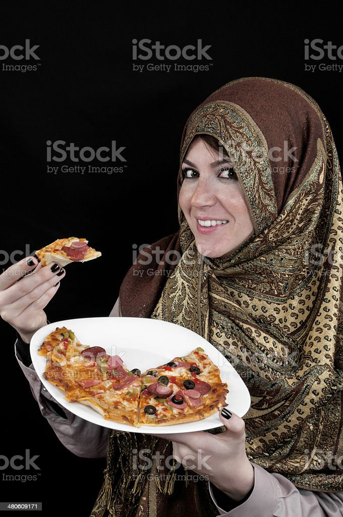 Muslim woman eating pizza royalty-free stock photo