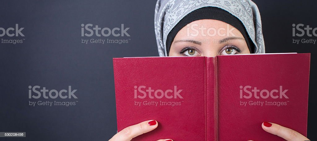 Muslim woman holding a book stock photo