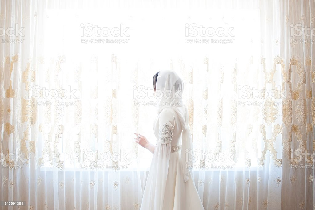 muslim woman in a white headscarf standing at the window stock photo