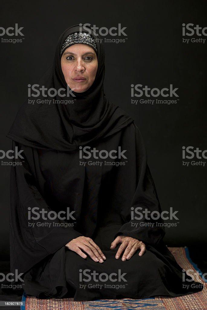 Muslim woman kneeling on black background stock photo