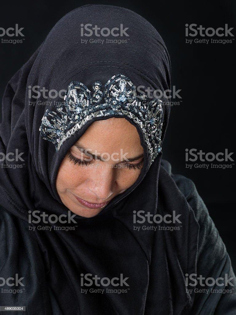 Muslim woman looking down stock photo