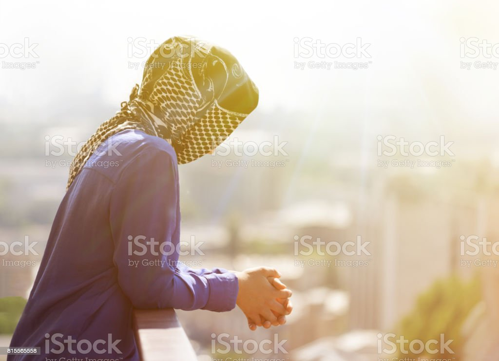 A Muslim woman looks at the sunset stock photo