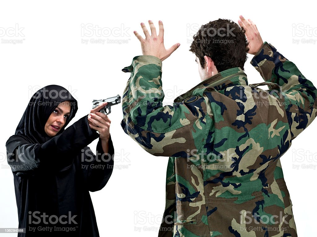 Muslim woman pointing a gun at a man wearing camouflage. royalty-free stock photo
