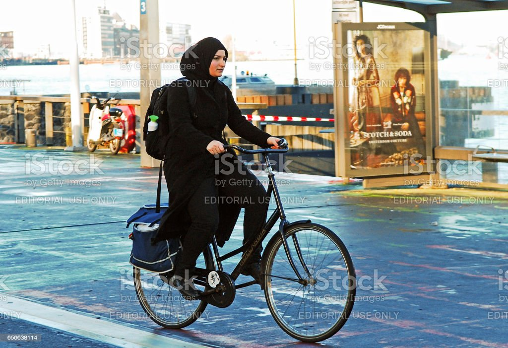 Muslim Woman riding a bicycle. stock photo