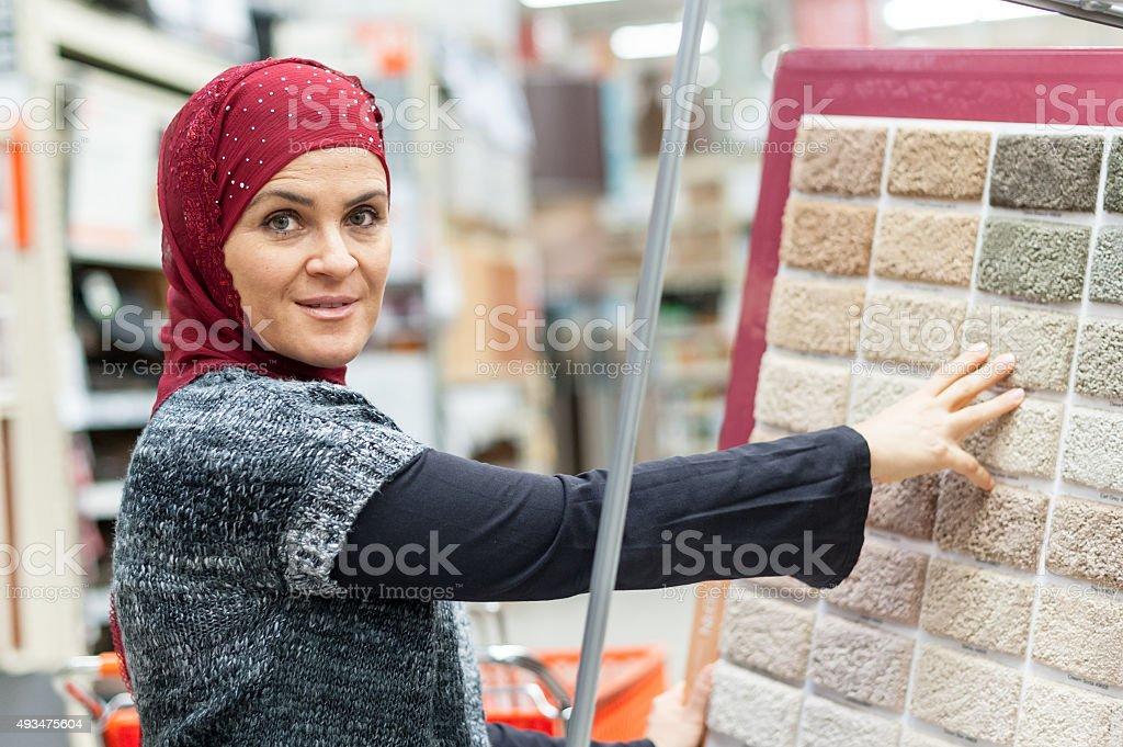 Muslim woman shopping for carpet stock photo
