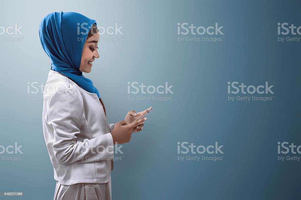 Muslim woman typing on cellphone stock photo