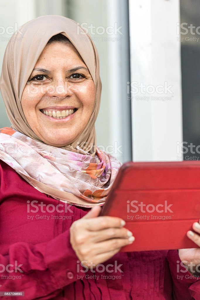 Muslim Woman using an Electronic Tablet stock photo