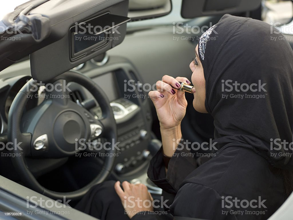 Muslim woman using her lipstick royalty-free stock photo