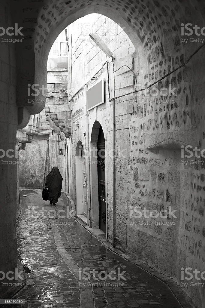 Muslim woman walking in alley of Sanliurfa Turkey royalty-free stock photo